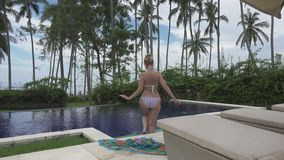 De camerabewegingen voor de jonge slanke vrouw aan bikini die naar het zwembad op tropisch gaan de toevlucht van Bali Indonesië stock videobeelden