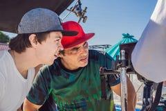De cameraexploitant, de directeur van fotografie en de directeur bespreken het proces van een commerciële videospruit stock foto