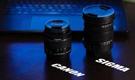 De cameralenzen Canon en de sigma op de lijst met blauw violet licht van het de achtergrond, laptop toetsenbord en de aanraking v royalty-vrije stock afbeelding