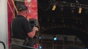 De cameraman schiet een stadium tijdens muziekoverleg stock video