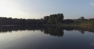 De cameravlucht over het meer, ontruimt als een spiegel Het wijst op de bomen op de kust, het groene gras, het blokhuis en het bl stock video