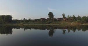 De cameravlucht over het meer, ontruimt als een spiegel Het wijst op de bomen op de kust, het groene gras, het blokhuis en het bl stock videobeelden