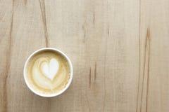 De cappuccino in document haalt kop op lichte houten lijst weg Stock Afbeelding