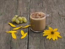 De cappuccinokop met een gele bloem en druiven wordt verfraaid die Royalty-vrije Stock Foto's