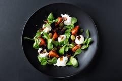 De Capresesalade met mozarella, tomaat, basilicum en balsemieke azijn schikte op zwarte plaat en donkere achtergrond Hoogste meni royalty-vrije stock afbeelding
