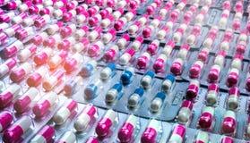 De capsulepillen van close-up roze-witte en blauw-witte antibiotica in blaarpak Antimicrobial drugweerstand farmaceutisch royalty-vrije stock fotografie