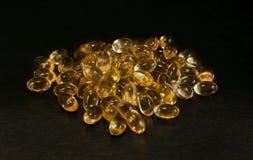 De capsules van de teunisbloemolie op een zwarte oppervlakte, met een ondiepe velddiepte stock foto's