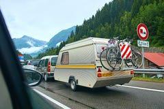 De caravan of de reisaanhangwagen met het hangen van fietsen maakte aan een auto op de alpiene weg in Zwitserse alpen vast royalty-vrije stock afbeeldingen