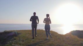 De cardiodietraining, het sportenmannetje en de vrouw met kanekalonvlechten lopen rond aan kant van rivier tegen hemel door helde stock video