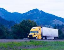 De cargaison jaune de remorque de cargueur de camion semi sur l'enroulement vert de route photo libre de droits