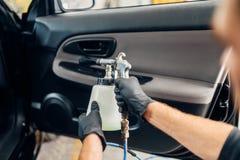 De Carwashdienst, mannelijke arbeider in handschoenen die nevel gebruiken stock fotografie