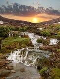 De cascade van dalingen op een zonsondergang in bergen Royalty-vrije Stock Afbeelding