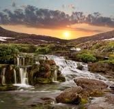 De cascade van dalingen op een zonsondergang in bergen Stock Foto