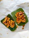 De cashewnoten bestrooien stroop op het groene blad stock afbeeldingen