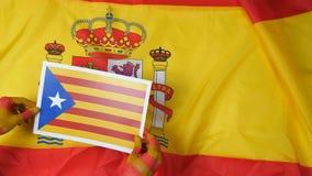 De Catalaanse handen zetten de vlag van Catalonië op de vlag van Spanje stock video