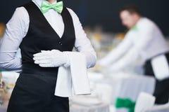 De cateringsdienst serveerster op plicht in restaurant stock afbeeldingen