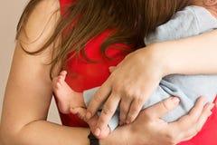 De Caucasoidmoeder houdt de pasgeboren baby in haar wapens en kust, zonder gezichten, tederheid en zorg, moeder en kind stock foto's