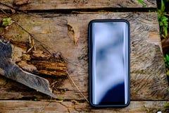 De celtelefoon op een houten plank die, in licht worden gebaad, vertroebelde achtergrond Stock Afbeeldingen
