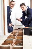 De Centrale verwarming van loodgieterand apprentice fitting binnenshuis stock afbeelding