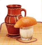 De ceramische kruik, een glas melk, een brood van brood. Stock Afbeelding