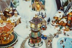 De ceramische miniatuur van Toy Christmas met snow-covered stad en model van lopende mensen Klein feestelijk dorp met klokketoren stock foto