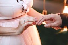 De ceremonie van het huwelijk De bruid in een roze kleding draagt een verlovingsring op een vinger aan de bruidegom Op haar is de stock foto