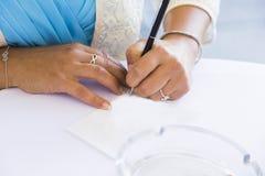 De ceremonie van het huwelijk Het meisje ondertekent huwelijksakte royalty-vrije stock afbeelding