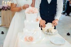 De ceremonie van het huwelijk De Scherpe Cake van de bruid en van de Bruidegom stock foto