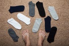 De chaos van sokken is als het vinden van een paar Benen tegen de achtergrond van verspreide sokken stock afbeeldingen