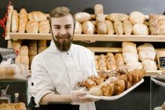 De charismatische bakker met een baard en een snor bevindt zich met een dienblad met verse gebakjes op de achtergrond van planken stock foto
