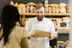 De charismatische bakker met een baard en een snor geeft een document zak brood aan de klant in de bakkerij stock fotografie