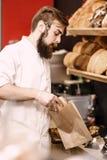 De charismatische bakker met een baard en een snor zet vers brood in een document zak in de bakkerij royalty-vrije stock afbeelding