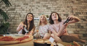 De charismatische dames in pyjama's hebben een prettijd die samen op een PlayStation-close-up voor de camera op spelen stock video