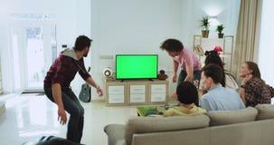 De charismatische groep vrienden die van buiten in de huiszitting snel komen op de bank en schakelt TV aan in stock video