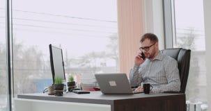 De charismatische jonge bureaumanager heeft een goede gelukkige dag in bureau die op telefoon spreken en aan laptop bij hetzelfde stock videobeelden