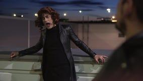 De charismatische kerel gekleed als vrouw, die zwarte kleren en pruik dragen, zingt buiten stock videobeelden