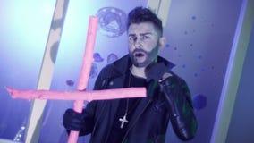De charismatische mens met leuk kapsel in leer danst en zingt met roze kruis stock footage