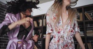 De charismatische twee dames in mooie pyjama's in de ochtend hebben het grote stemming springen opgewekt over bed in een moderne  stock video