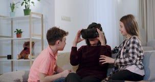 De charismatische twee jonge geitjes en een grootmoeder op de bank die een VR, jonge geitjes onderzoeken hebben een pret hoe oma  stock video