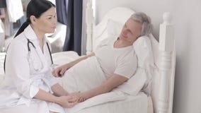 De charmante arts behandelt een gehandicapte hogere mens in bed stock videobeelden