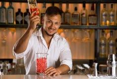 De charmante barman giet alcohol van een fles in een mengelingskop Stock Fotografie