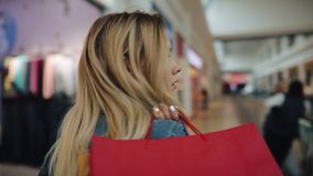 De charmante blondevrouw houdt het winkelen zakken op haar schouder lopend rond de wandelgalerij stock video