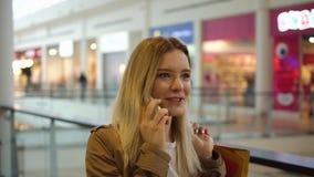 De charmante blondevrouw spreekt op de telefoon lopend met het winkelen zakken in de wandelgalerij stock videobeelden