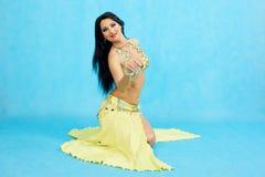 De charmante danser voert oosterse buikdans op een blauwe achtergrond uit royalty-vrije stock foto