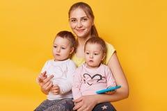 De charmante hartelijke brijzitting met haar leuke kleine dochters op vloer in gele studio, terloops geklede wijfjes, ziet eruit royalty-vrije stock foto's