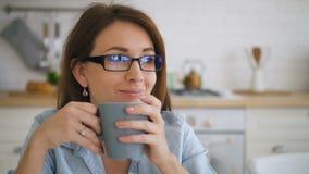 De charmante huisvrouw drinkt koffie, zittend bij lijst in keuken van flat stock video