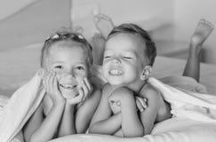 De charmante kinderen die op het bed spelen Stock Afbeeldingen