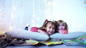 De charmante meisjes spelen samen en babbelen, liggend op vloer en op hoofdkussens tegen muur met slinger en Kerstboom stock videobeelden