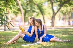 De charmante, mooie en jonge meisje-studenten lezen boeken en kijken gelukkig in het park Twee meisjes die een boek lezen Royalty-vrije Stock Fotografie