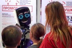 De charmante promotorrobot communiceert met bezoekers royalty-vrije stock afbeeldingen